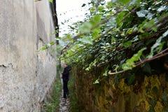 Schmale Dorfgasse mit Steinwänden Stockfotos