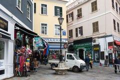 Schmale Straße der Stadt mit kleinen Shops und gehenden Leuten Stockbilder