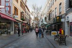 Schmale Straße der Stadt mit kleinen Shops und gehenden Leuten Lizenzfreies Stockfoto