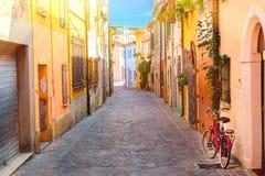 Schmale Straße des Dorfs der Fischer San Guiliano mit bunten Häusern und einem Fahrrad am frühen Morgen in Rimini, Italien Stockfotografie