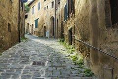 Schmale Straße, die in eine Stadt von Toskana steigt Lizenzfreie Stockbilder
