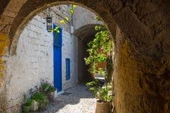 Schmale Straße mit alten mittelalterlichen Bögen und blaue Tür in Rhodos-Schleppseil Rhodos-Insel, Griechenland lizenzfreies stockfoto