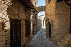 Schmale Straße mit alten mittelalterlichen Bögen und blaue Tür in Rhodos-Schleppseil Rhodos-Insel, Griechenland stockfotografie