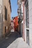 Schmale Straße mit einem roten Gebäude in Madrid, Spanien Lizenzfreie Stockfotografie