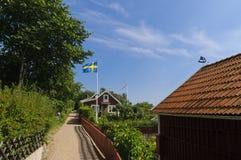 Schmale Straße und rote Häuschen in Schweden Lizenzfreies Stockbild