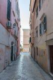 Schmale Straße mit Steinbeschaffenheitsabschlussgebäuden Stockfotos