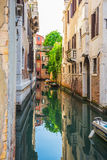 Schmaler Kanal unter alten bunten Backsteinhäusern in Venedig stockfotografie