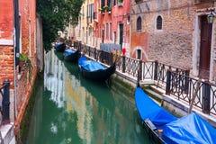 Schmaler Kanal Venedigs mit Gondeln, Italien Venedig-Straßenkanal mit Booten entlang Backsteinhäusern lizenzfreie stockbilder