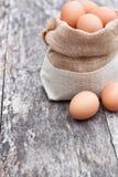 Schmeißen Sie Tasche mit Eiern auf der alten Tabelle raus Lizenzfreies Stockbild