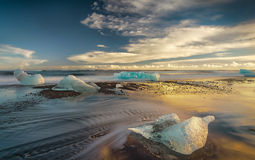 Schmelzende Eisberge auf dem Ufer bei Sonnenuntergang Stockbild