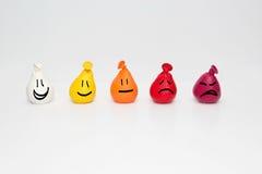 Schmerz-Skala-Diagramm für Kinder Kritzeln Sie smileygesichter auf kleinen Farbabstufungsballonen Stockfotos