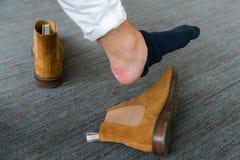Schmerzliche Fersenwunde bemannt an die Füße, die durch neue Schuhe verursacht werden Gebrochenes ter stockbilder
