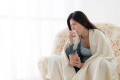 Schmerzliche Frau, die auf dem entspannenden Lehnsesselsofa sitzt Lizenzfreie Stockfotos