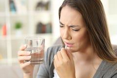 Schmerzliche Frau, die eine Pille einnimmt Lizenzfreies Stockbild