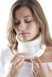 Schmerzliche Frau, die zervikalen Kragen trägt Stockfoto