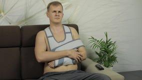 Schmerzlicher, gebohrter Mann mit einer tragenden Armklammer des gebrochenen Armes, die auf einem Sofa sitzt stock video footage