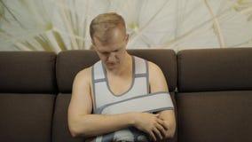 Schmerzlicher, gebohrter Mann mit einer tragenden Armklammer des gebrochenen Armes, die auf einem Sofa sitzt stock footage
