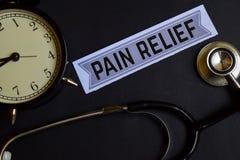 Schmerzlinderung auf dem Papier mit Gesundheitswesen-Konzept-Inspiration Wecker, schwarzes Stethoskop stockfotografie
