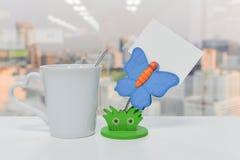 Schmetterlingspapierinhaber eines Schuldtitels und ein Tasse Kaffee Lizenzfreies Stockbild