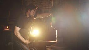 Schmied behandelt den Druck des Werkstückes vom geschmolzenen Metall ein Mann in der Funktionskleidung Langsame Bewegung stock video