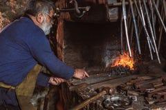 Schmied bei der Arbeit mit glühenden Eisen lizenzfreies stockbild