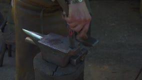 Schmied, der das fl?ssige Metall auf dem Ambosse in der Schmiede schmiedet stock video footage