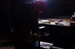 Schmied, der in einer Schmiede in der Hintergrundbeleuchtung arbeitet Alter Kompass und Seil auf Leinwand Stockfotografie