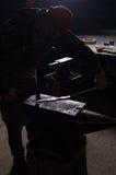 Schmied, der in einer Schmiede in der Hintergrundbeleuchtung arbeitet Alter Kompass und Seil auf Leinwand Stockbild