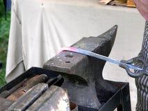 Schmied, der glühendes Eisen verbiegt stockbild