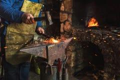 Schmied, der manuell das flüssige Metall auf dem Ambosse in der Schmiede schmiedet stockbild