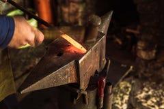 Schmied, der manuell das flüssige Metall auf dem Ambosse in der Schmiede schmiedet lizenzfreie stockbilder
