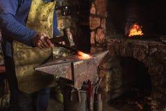 Schmied, der manuell das flüssige Metall schmiedet lizenzfreie stockfotografie