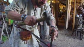 Schmied, der mit einem Metallteil auf stithy in der Schmiede arbeitet stock footage