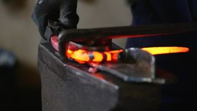 Schmied, der mit heißem glühendem Metall, verbiegender Stahl in einem smithery, Zeitlupe arbeitet stock footage