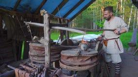 Schmied, der mit Schmiedepelzen in der Schmiede arbeitet stock footage
