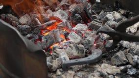 Schmied korrigiert Kohlen in einem Messingarbeiter und in einem Störfeuer vom Hufeisen stock video footage