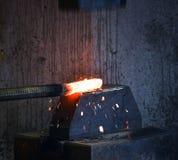 Schmied schmiedet ein glühendes Eisen Stockbild