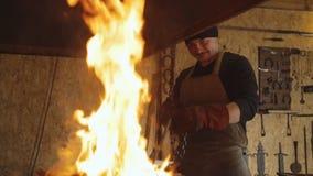 Schmied setzt Metallbillet auf Kette in Ofen ein, um ihn zu erhitzen stock footage