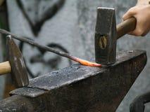 Schmiede, die an einem Metalldetail arbeiten Lizenzfreies Stockfoto