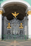 Schmiedeeisengrilltor mit dem Kaiserdoppelköpfigen adler und das Monogramm auf dem Eingang des Winter-Palastes St. Petersbu Lizenzfreie Stockbilder