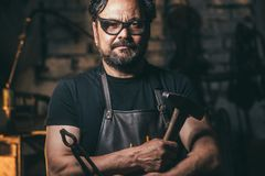 Schmiedeporträt mit Bart in der Werkstatt lizenzfreie stockfotos
