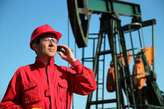 Schmieröl-Arbeitskraft, die Handy nahe bei Pumpjack verwendet Lizenzfreies Stockbild