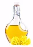 Schmieröl in einer Flasche mit Rapssamenblumen stockfotografie