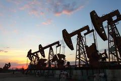 Schmieröl pumpen untergehende Sonne gegen Lizenzfreie Stockfotos