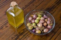 Schmieröl und Oliven über hölzerner Tabelle. Lizenzfreie Stockfotos