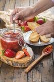Schmieren der Erdbeermarmelade auf einem Toast zum Frühstück stockfoto