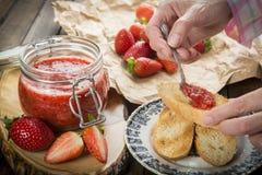 Schmieren der Erdbeermarmelade auf einem Toast zum Frühstück lizenzfreies stockfoto