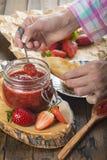 Schmieren der Erdbeermarmelade auf einem Toast zum Frühstück stockbild