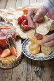 Schmieren der Erdbeermarmelade auf einem Toast zum Frühstück stockfotos