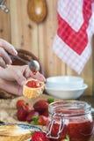 Schmieren der Erdbeermarmelade auf einem Toast zum Frühstück stockfotografie